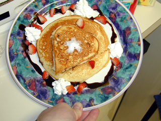 really yummy looking pancakes with berries, chocolate, and whipped cream.